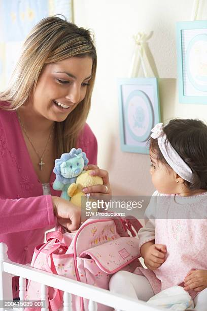 Young mother with baby girl (12-15 months) and toys