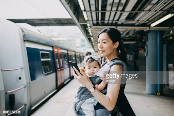 Young mother with baby girl using smartphone while waiting for subway in subway station platform