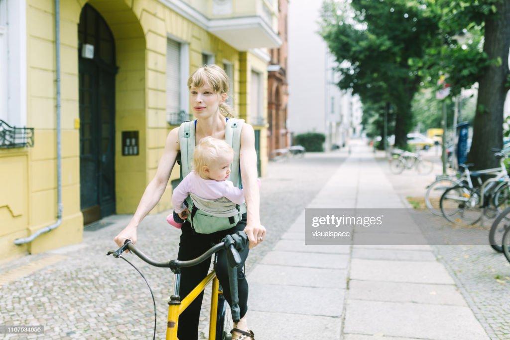 キャリアの赤ちゃんを持つ若い母親は、街を自転車に乗って : ストックフォト