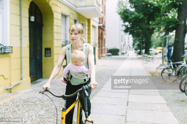 young mother with baby in the carrier riding the bike through the city - central berlin stock pictures, royalty-free photos & images