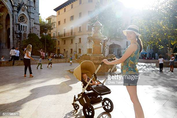 Young mother with baby stroller in city