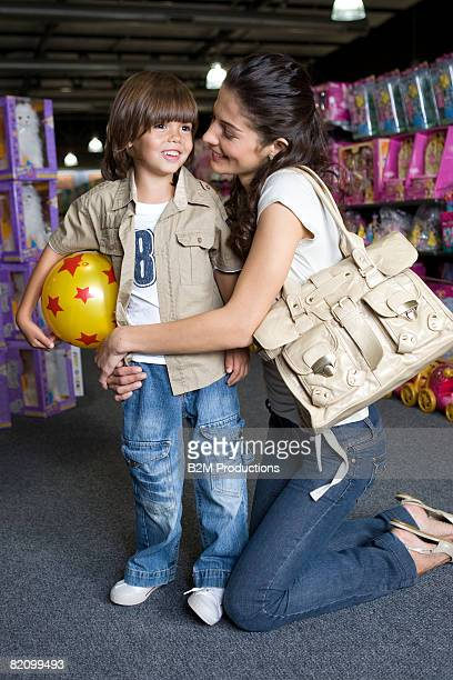 young mother with child (4-5 years) in toy store - 25 29 years stock pictures, royalty-free photos & images