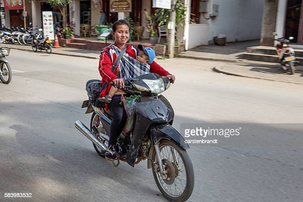 Young mother with child on a motorbike