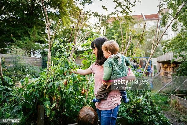 Young mother with children in community garden