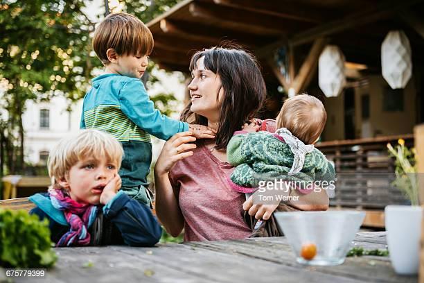 young mother with children sitting in a community - ein elternteil stock-fotos und bilder
