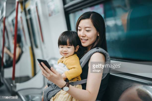young mother with cute little daughter using and looking at smartphone with joy while riding on subway - 専業主婦 ストックフォトと画像