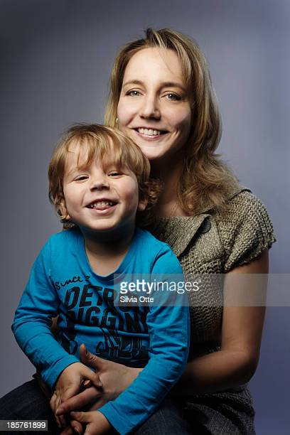 young mother with her 3 year old boy smiling - mom sits on sons lap stock pictures, royalty-free photos & images