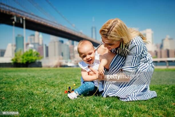 Young mother with her baby girl near Brooklyn bridge in USA