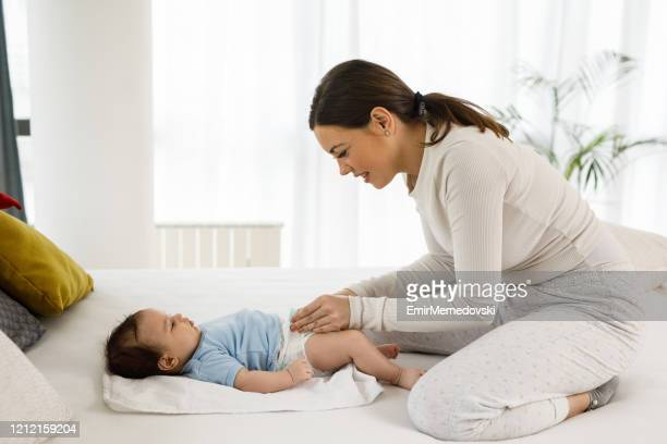 young mother with her little baby boy at home changing diapers - mum changing nappy stock pictures, royalty-free photos & images