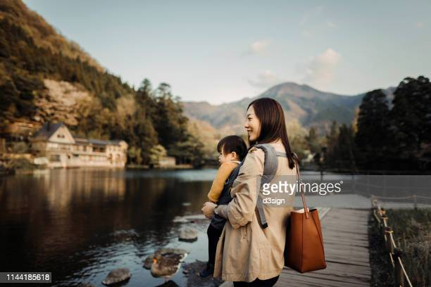 young mother with little daughter sightseeing at lake relaxing and enjoying the beautiful scenics - satoyama scenery stock pictures, royalty-free photos & images
