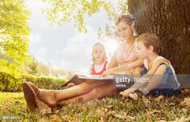 Young mother with son and daughter reading book