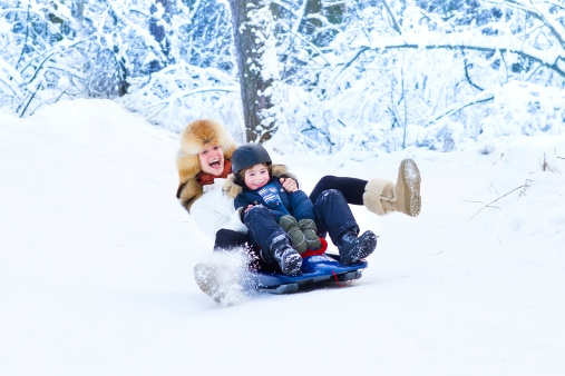Young mother with son on sleigh ride in snowy park 512420927