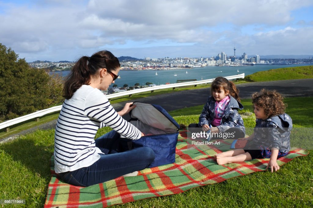 Young mother with two daughters having a picnic : Stock Photo