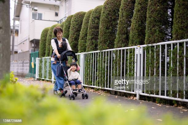 young mother with two little children visiting public park - pushchair stock pictures, royalty-free photos & images
