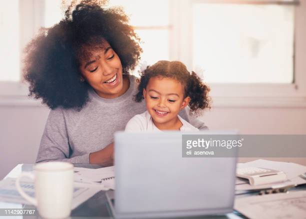 young mother working and spending time with her daughter - working mother stock pictures, royalty-free photos & images