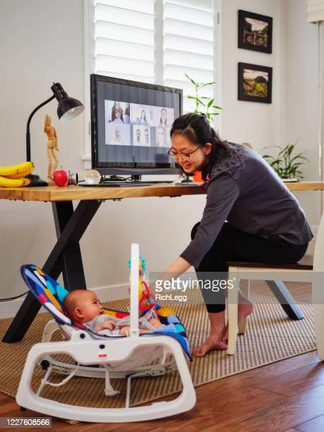 junge mutter arbeitet von zu hause aus auf einer videokonferenz - mother daughter webcam stock-fotos und bilder