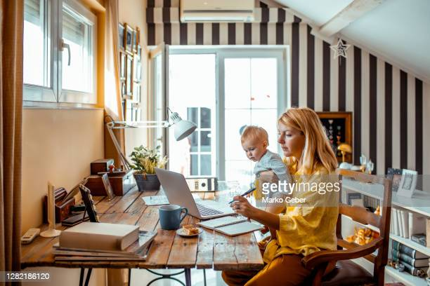 young mother working from home - economy stock pictures, royalty-free photos & images
