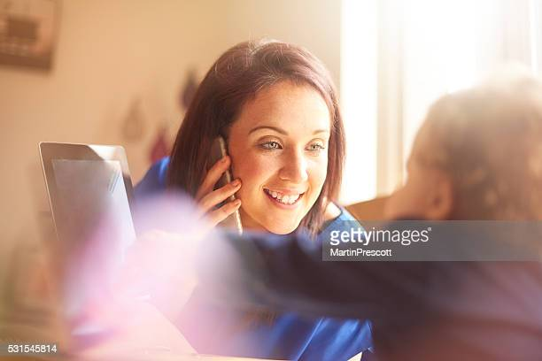 Young mother working from home with toddler