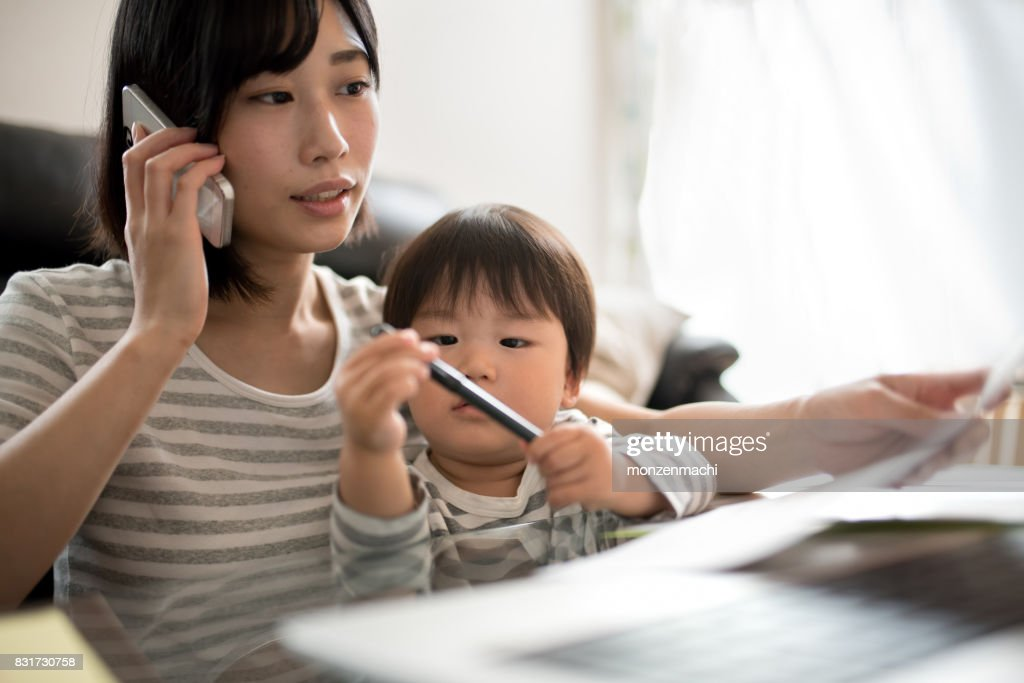 young mother working in house with her child : Stock Photo