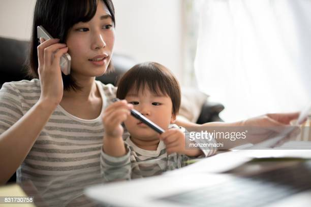 young mother working in house with her child