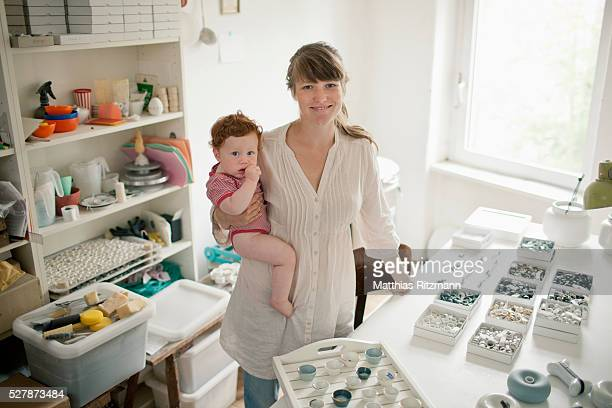 young mother working with child (6-12 months) on her lap - 12 23 months stock pictures, royalty-free photos & images