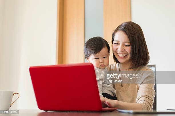 young mother working with her baby girl at home - desktop pc stockfoto's en -beelden