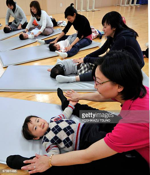Young mothers holding their babies with babyslings stretches before starting in samba dances called babydance at a studio in Yokohama city suburban...
