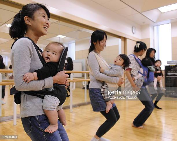 Young mothers holding their babies with babyslings train in samba dances called babydance at a studio in Yokohama city suburban Tokyo on March 24...