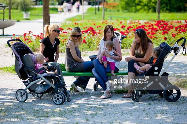 Young mothers in a park walking their babies...resting