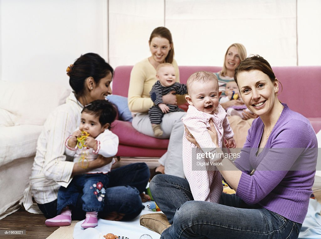 Young Mothers Playing with Babies in a Living Room : Stock Photo