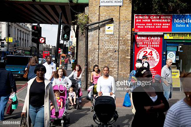 Young mothers push their babies in prams on Brixton Road, a multicultural area in South London. This is on the corner of Atlantic Road underneath the...