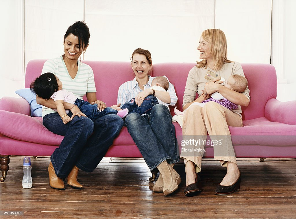 Young Mothers with Their Babies on a Pink Sofa : Stock Photo