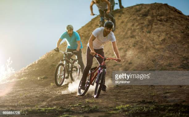 Young mountain bike cyclists racing on dirt road.
