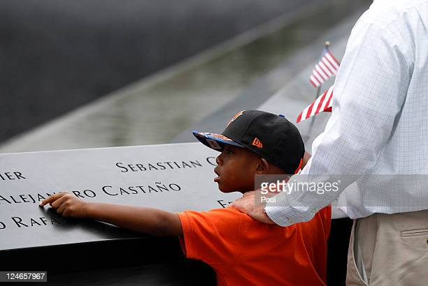 A young mourner touches the names of the lost loved ones during tenth anniversary ceremonies of the September 11 2001 terrorist attacks at the World...