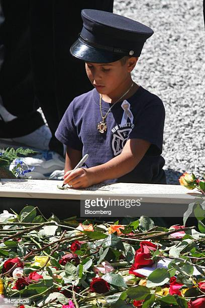 A young mourner wearing a New York Fire Department dress uniform cap and a FDNY tee writes a message on the edge of a reflecting pool during the...