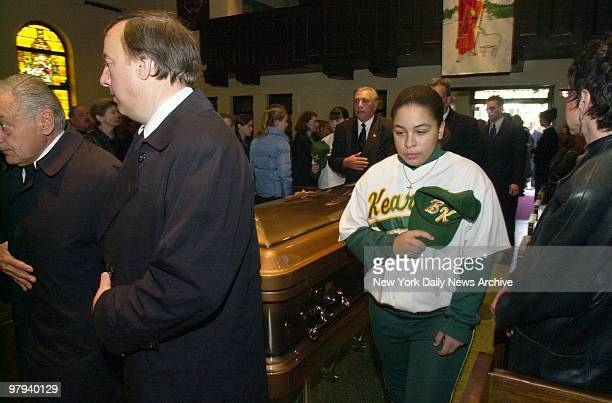 Young mourner wears her Bishop Kearney High School junior varsity softball team jersey as she stands by the coffin of her coach Franco Pomponio...