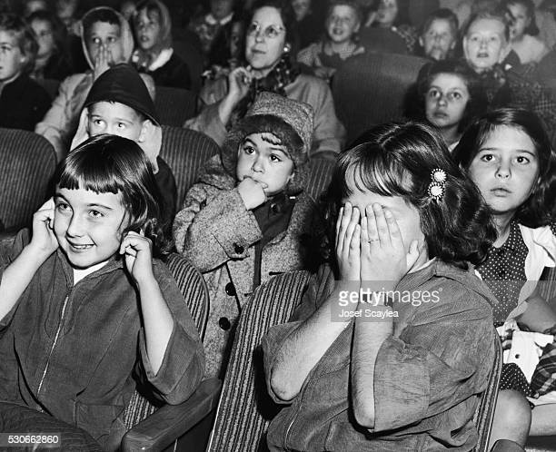 Young moviegoers react to a frightening scene in a Saturday matinee feature at the movie theater | Location Northgate Seattle Washington USA