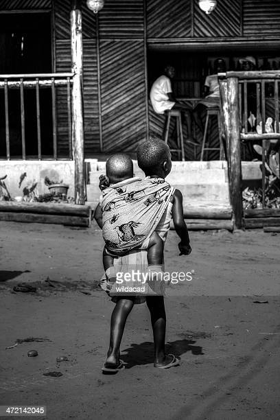 Young Mozambican child carries her sister