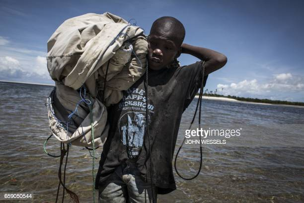 A young Mozambican fishermn makes his way back to the shore with his sail after a day of fishing on February 16 2017 in Palma where large deposits of...