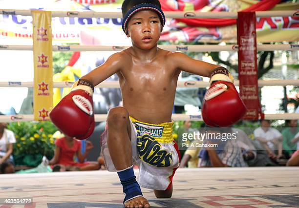 A young Muay Thai boxer performing a ritual dance before a fight at king Taksin's birthday celebration in Bangkok