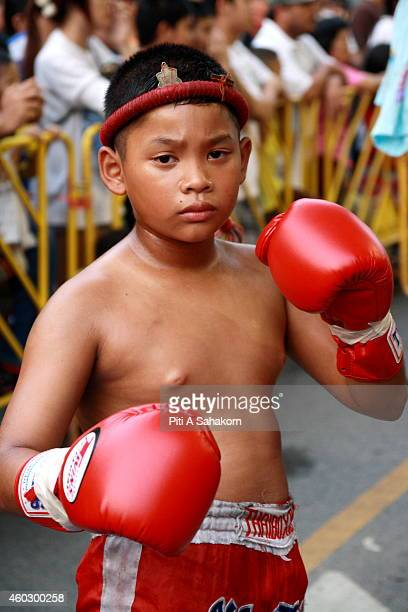 A young Muay Thai boxer pose for photograph before get in the ring at king Taksin birthday celebration in Bangkok