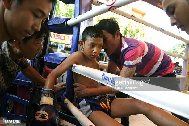A young Muay Thai boxer resting and getting coached between rounds in his corner during a fight at king Taksin's birthday celebration in Bangkok