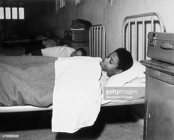 A young mulatto boy at bed covered with a sheet in a dormitory with other boys who are mulattoes too they stay in the Village of the Children a care...