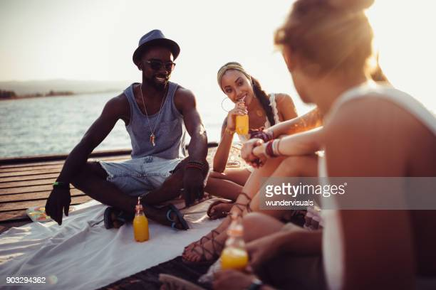 Young mulit-ethnic hipster friends relaxing with drinks on jetty
