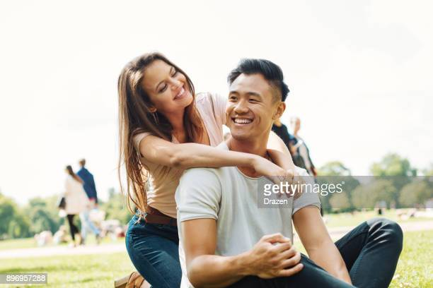 Young multi ethnic couple hugging in park