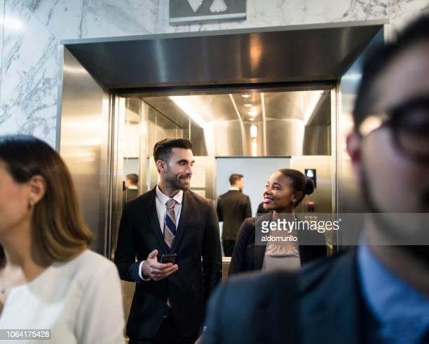 jonge multi-etnische bedrijfsleiders lopen van de lift - nosotroscollection stockfoto's en -beelden