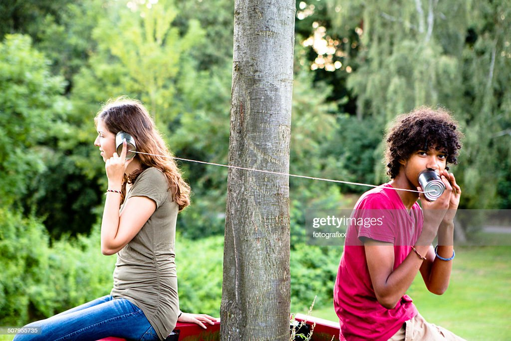 young multi-ethnic couple communicate with a tin can phone : Stock Photo