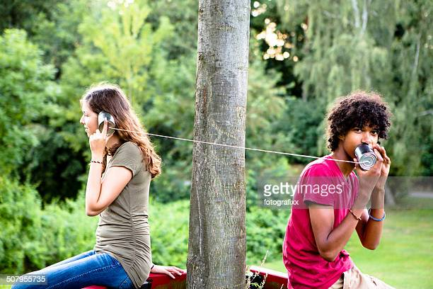 young multi-ethnic couple communicate with a tin can phone