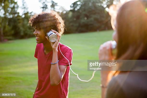 Junge multi-ethnischen paar Kommunikation mit einem Dosentelefon