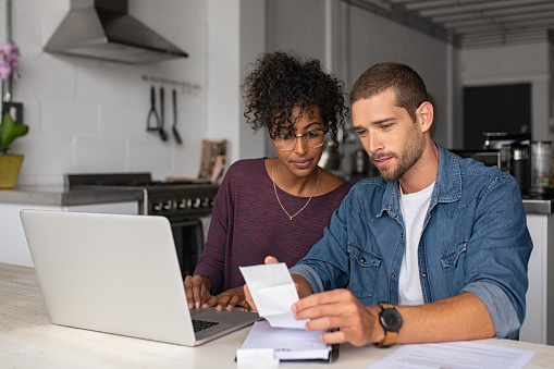 Young multiethnic couple examining home finance 1158243057
